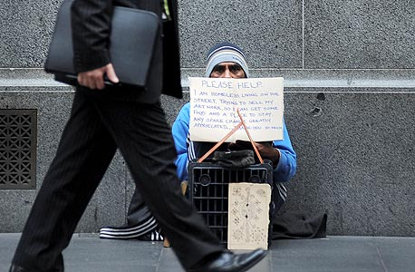 """איש עסקים חולף על פני הומלס בסידני, אוסטרליה. """"בצמרת שוק העבודה, כשאנשים יכולים לקבוע את השכר של עצמם, מאוד קשה לעמוד בפיתוי"""""""