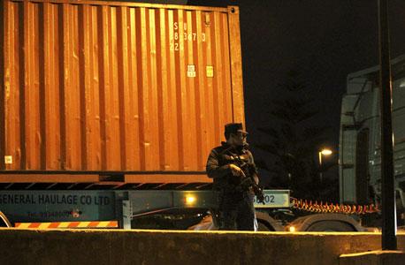 שוטר קפריסאי שומר על מכולה ובה כסף שעשתה דרכה לאחד הבנקים באי