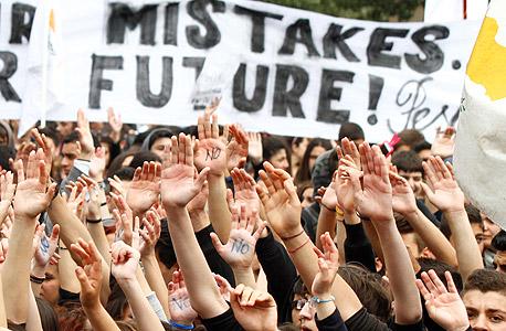 """סטודנטים מפגינים נגד תנאי החילוץ בקפריסין. """"הבנקים שם רצו להיות מרכז פיננסי, הם הבטיחו למפקידים ריבית גבוהה ומשכו השקעות מעל ומעבר לגודל של כל הכלכלה שלהם"""""""