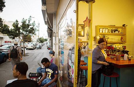 אפריקאים וישראלים בבית קפה. בלב העיר גונבים יותר זוגות אופניים