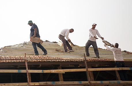 """מניחים את הרעפים על גג בית המתמחים, שיהפוך למרכז החינוכי הארצי של כי""""ח, צילום: תומי הרפז"""