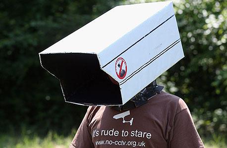 חבר בארגון NO CCTV, המתנגד לשימוש במצלמות אבטחה בערי בריטניה, מפגין בוועידה