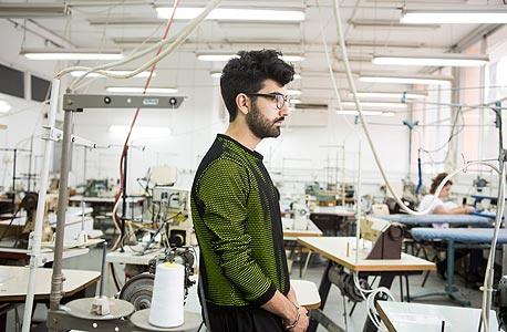 גוסטבו בחדר מכונות תפירה בשנקר. לובש סווטשירט בעיצובו.