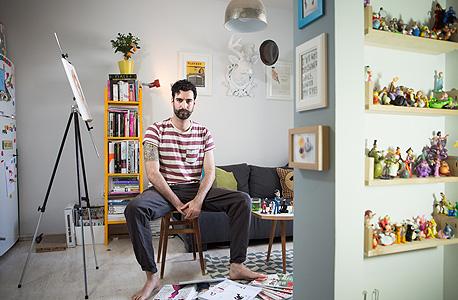 """נמרוד בסלון ביתו. לובש טי שירט של H&M ומכנסיים  מ־asos. משמאל דאלי. """"תמיד היתה לי נטייה לדברים של פעם"""""""