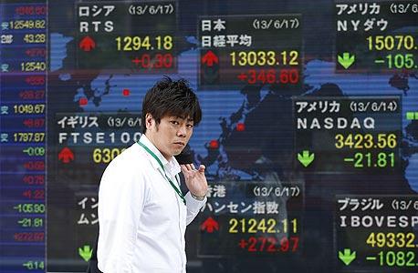 """סוחר על רקע מסכים המראים את הירידות בשוק היפני בסוף השבוע שעבר. """"אתה מתחיל לראות סדקים בביטחון המשקיעים"""""""