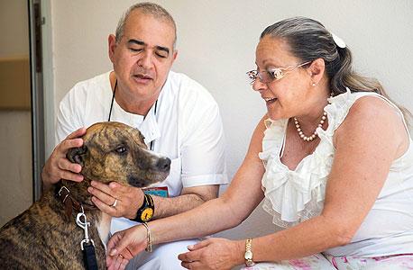 """ד""""ר מיקי ברקוביץ' והאח שמוליק בן טל עם כלב של אחד החולים"""