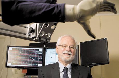 """דונהיו במעבדתו באוניברסיטת בראון. בצג מאחוריו מופיעה """"שירת המוח"""": רישום הפעילות החשמלית של עשרות נוירונים שהוא מנסה לפענח. """"כרגע נחוצה טכנולוגיה פולשנית"""""""