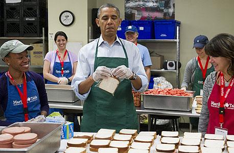 הנשיא אובמה מתנדב בבית תמחוי עם עובדי הממשל המושבתים, צילום: איי אף פי