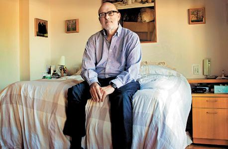 """ארני דרוק בביתו ביפו. ברקע: עבודה גדולה של ירדן וולפסון ועבודות קטנות של דוד ניפו ופול ריילי. """"כואב לי, לא מבינים את החשיבות של כל הפריטים באוסף"""""""