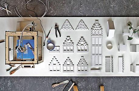 מדפסת תלת-ממד קטנה מייצרת את רכיבי דגם הבניין