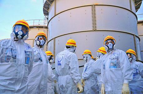 עובדים לבושים בחליפות נגד קרינה רדיואקטיבית לאחר האסון בפוקושימה, מרץ 2011