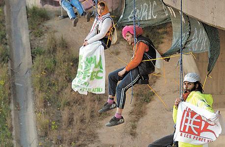 """צעירים תלויים מגשר בברצלונה במחאה על מעצרו של אנריק דוראן, """"רובין הוד של הבנקים"""""""