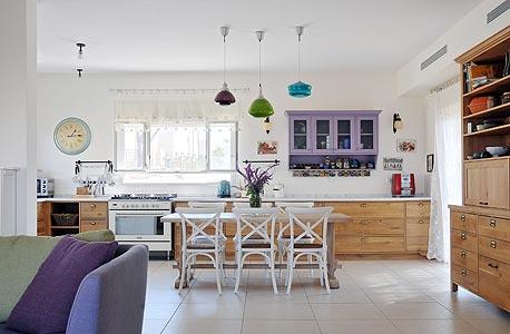 """בית בעיצוב מרב זהר. שילוב של כתמי צבע עם פריטי וינטג' כמו כורסה ששוחזרה בהדפס מודרני, שולחן שרגליו נצבעו ב""""גרביים"""" וכוננית משופצת"""