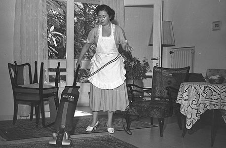 אשה מנקה סלון בתל אביב, 1949. רהיטים קלים מחומרים זולים שאפשר לנייד בקלות