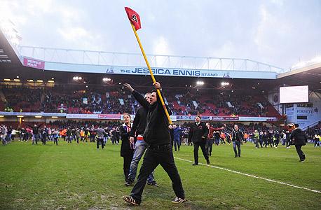 """אוהד כדורגל אנגלי. קבוצת המחוקקים מבקשת להטיל גם חוקים שיגנו על ה""""נכסים"""" של הכדורגל שהם בעלי ערך לקהילה, כמו הצבעים של מועדון, השם והבעלות על המגרש הביתי."""