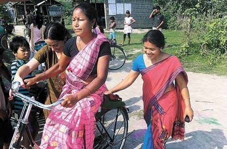 תושבת האי לומדת לרכוב על אופניים. במקום ללכת שעות ברגל לכפר השכן