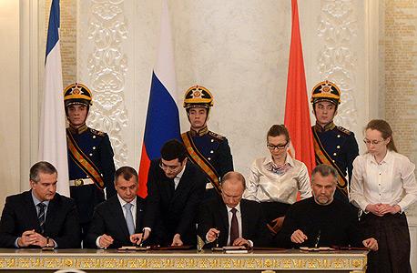 ולדימיר פוטין חותם על סיפוח קרים לרוסיה, צילום: איי אף פי
