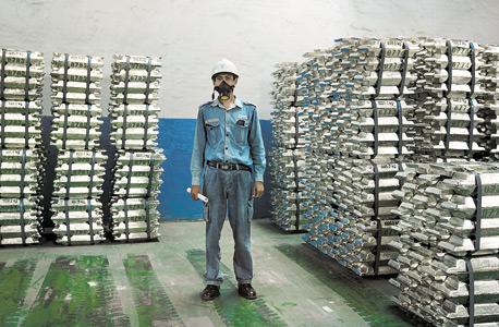 פועל במחסני תאגיד הבדיל פי.טי טימה. 100 אלף טונות מאדמת האי לסדנאות בסין, צילום: Matilde Gattoni