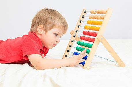 """ילד משחק עם חשבוניה. """"הילדים האחרונים שמצטרפים הם הרווח של הגן"""""""