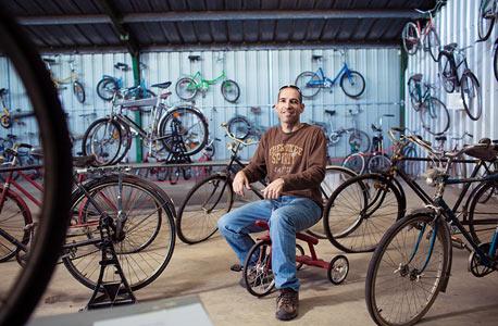 """אלון וולף, מפעיל את מוזיאון האופניים הראשון בארץ . """"בכל יום אני בטלפונים עם אנשים שמציעים לתרום פריט, ואני מבלה לא מעט זמן באיסופים. יש לי מחסן של כל אופני הג'אנק ההרוסים ובכל כמה זמן אני מוציא זוג אחד ומשפץ אותו. ואני לא זורק כלום כי מהחלקים של האופניים אני גם בונה פסלים"""""""