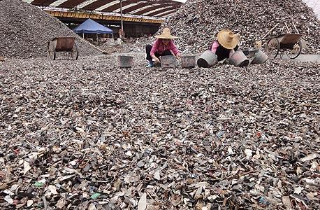 """""""שדה"""" של מכוניות גרוסות בפושאן, סין. הפועלים עובדים במיון החתיכות שרובן מגיעות מארה""""ב """"שנפטרת מ־14-10 מיליון מכוניות בשנה"""""""