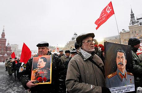 """חוגגים את יום הולדתו ה־132 של סטלין במוסקבה, ב־2011. """"הקפיטליסטים יוכלו לצאת מהמשבר בזחילה על ארבע. הם לא ימצאו מוצא שלא יפריע לאינטרסים שלהם"""""""