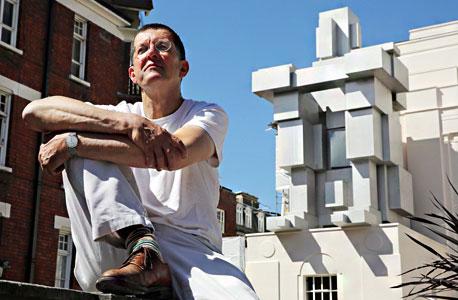 """האמן אנטוני גורמלי יושב לפני עבודתו ROOM. """"רחם או תא מרופד"""", צילום: אימג"""