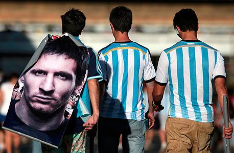 אוהדי נבחרת ארגנטינה עם פוסטר של ליאו מסי מונדיאל 2014, צילום: רויטרס