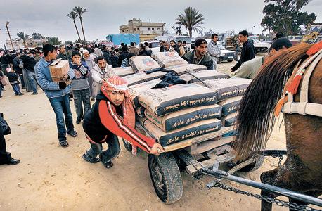 פלסטיני דוחף עגלה עמוסה במלט שהועבר ממצרים לרצועה