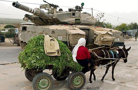 """פלשתינאית עם חמור רתום ל עגלה חולפים על פני טנק של צהל ב עזה, צילום"""" שאול גולן"""