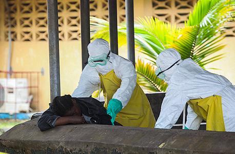 מגיפת האבולה. פינוי גופה בליבריה, צילום: אי פי איי