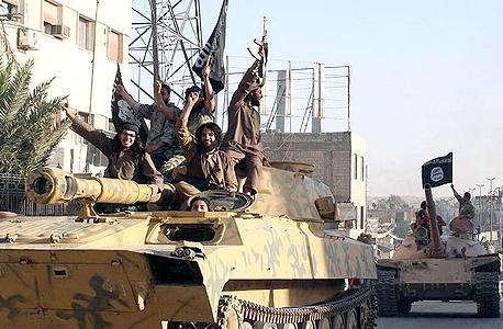 לוחמי דאעש על טנק שנלקח כשלל לחימה סוריה, צילום: איי פי