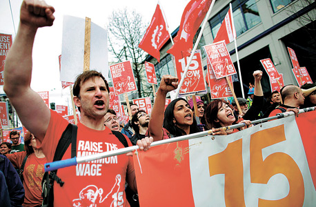 """מפגינים בקמפיין להעלאת שכר המינימום בסיאטל, שהנאואר היה ממוביליו. """"15 דולר לשעה זה לא הימור מסוכן — זו השקעה באסטרטגיה מנצחת"""""""