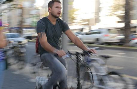 רוכב על אופניים חשמליים בתל אביב. פקחים יוכלו להורות על פינוי דרך, להוציא אוויר מגלגלי אופניים, לגרור אופניים ואף לתת קנסות לרוכבים