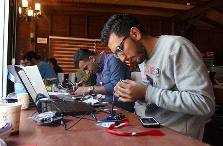 """איאד אל־ג'ואריש (מלפנים) ומוחמד קבאג'ה, מרכיבים מכונית שמדווחת לנהג מרחוק. """"אני מת לעבוד בחברה ישראלית, אבל אין אופציות"""""""