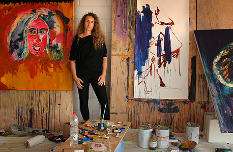 """ענת פרופר גולדנברג בסטודיו שלה, על רקע דיוקן עצמי. """"כשהציגו אותי בלי ה'פרופר' אמרתי: עשיתי שלום עם כל הצדדים של השם שלי, עם ענת, עם הפרופר ועם הגולדנברג"""""""