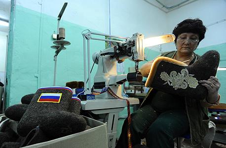פועלת במפעל מחוץ לסנט פטרסבורג מכינה מגפי לבד מסורתיים לחורף, צילום: איי אף פי