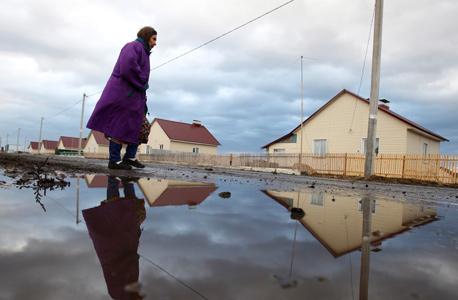 אשה בכפר הרוסי הנטוש נובומוסילונובה.   תמותת הגברים השאירה כפרים שבהם חיות רק נשים מבוגרות
