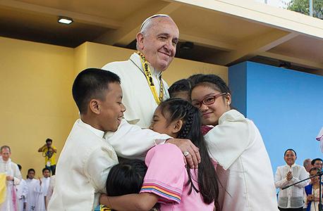 האפיפיור פרנציסקוס מחבק ילדים בביקורו השבוע בפיליפינים