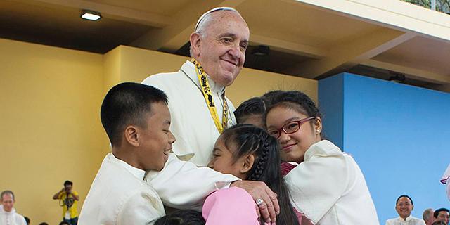 האפיפיור פרנציסקוס מחבק ילדים בביקורו השבוע בפיליפינים, צילום: בלומברג