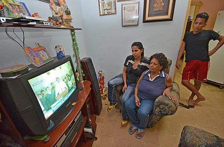 משפחה קובנית צופה בטלוויזיה. משכורת ממוצעת של 20 דולר בחודש