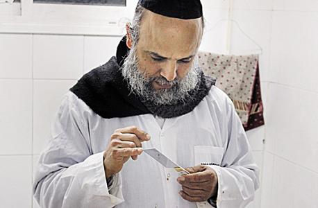 """הרב חננאל יפעי בודק סכין. """"מקרה האלימות היחיד כאן היה כשאחד הפלסטינים עצבן את השוחטים, והשוחט היהודי שיסף לו את הבטן"""""""