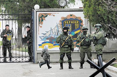 """חיילים רוסים (מקדימה) ואוקראינים (מאחורי השער) באוקראינה, במאי. """"כשפוטין רוצה להיות פופולרי הוא יוצא למלחמה"""""""