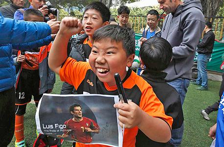 """אוהד כדורגל סיני צעיר. """"הכדורגל הוא ספורט פופולארי אבל לא משחקים אותו"""""""