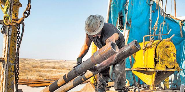 """עובד בתעשיית הנפט בארה""""ב. מספר המשרות צנח ב-70 אלף מאז השיא באוקטובר 2014, צילום: בלומברג"""