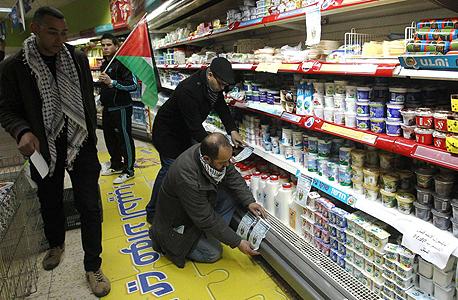 פעילים תולים עלונים הקוראים לחרם מוצרים מישראל במכולת בבית לחם
