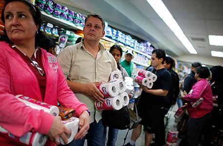 קונים בסופרמרקט בקרקס אוגרים חבילות של נייר טואלט