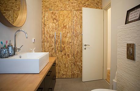 חדר האמבטיה, הכולל ארון גדול משבבי עץ OSB ובו מכונת כביסה ומייבש וארגז החול של החתולות. כמה שיותר מקומות אחסון
