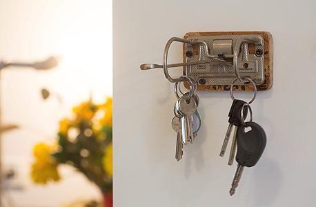 מתלה למפתחות שעשוי מלוח עץ ומנגנון של קלסר. מתנה ממעצב תעשייתי