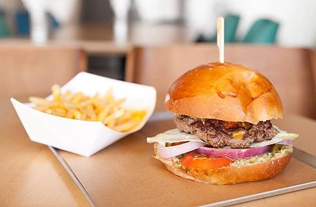 ארוחת בייסיק בטראק דה לוקס: המבורגר עם בייקון וצ'דר בלחמניית בריוש וצ'יפס ברוטב גבינה. מושחת